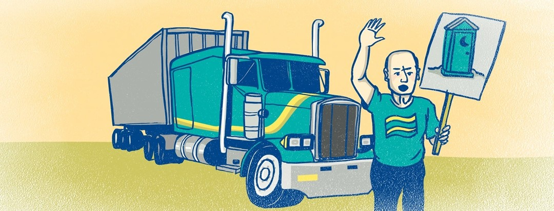 A man holds a protest sign with a port a potty on it in front of his big rig