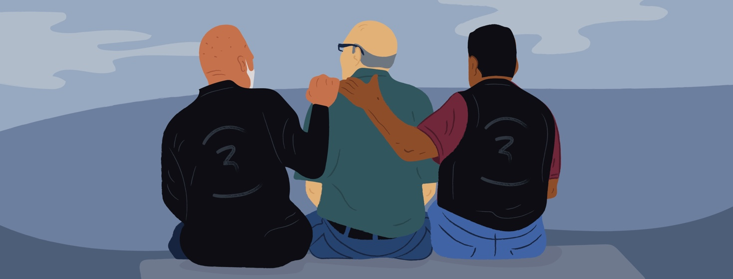 Three older men, sitting on a bench with their arms around each other