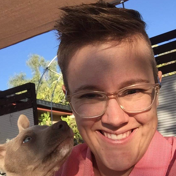 Charise smiles with a light brown dog