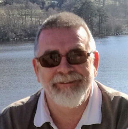 Gerry smiles for a sunny photo in front of a body of water