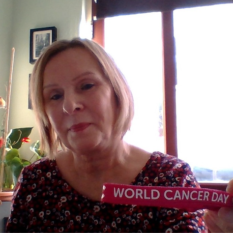 """Linda looks at the camera holding a ribbon that says """"World Cancer Day"""""""