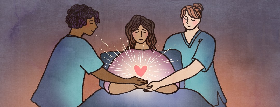 Two nurses help a patient hold a glowing heart.