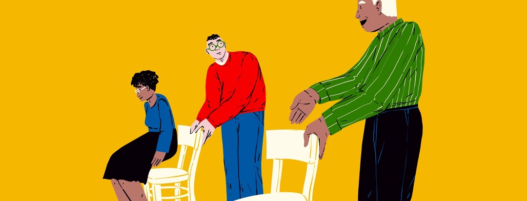 A male caregiver pulls out a chair for a woman, and looks over to his left where another man is pulling out a chair for the caregiver.