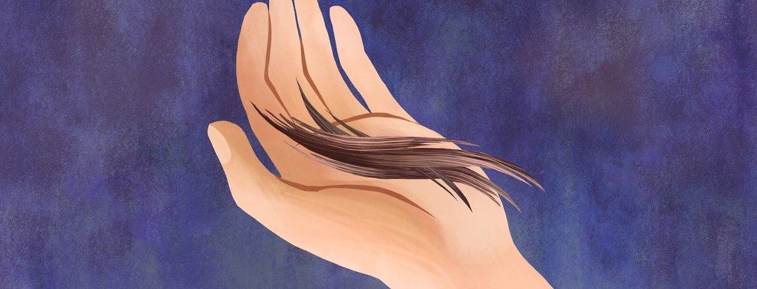 Close-up of a person holding pieces of hair in their hand.