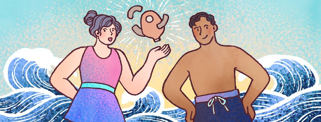 A woman and man in swimsuits hold up an ostomy bag with barrier strips, as waves roll behind them.