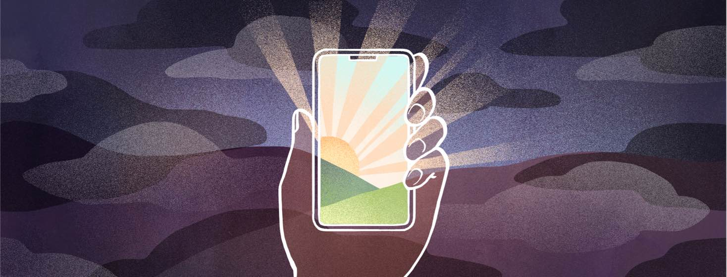 Surrounded by a dark landscape, a person's hand holds a phone that shows a rising sun over bright hills.