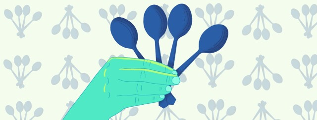 A hand holding four spoons
